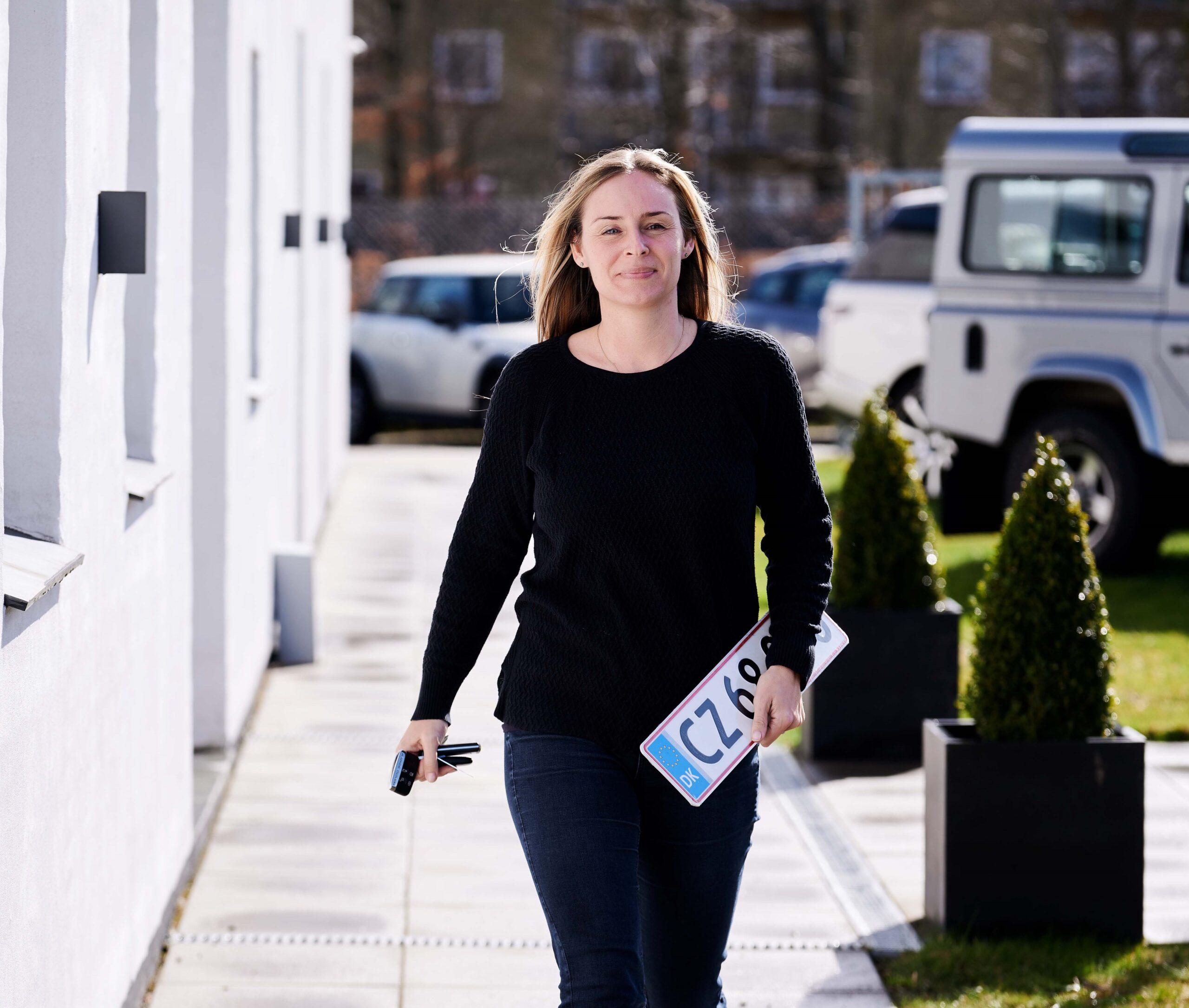 Kvinde går med en nummerplade i hånden