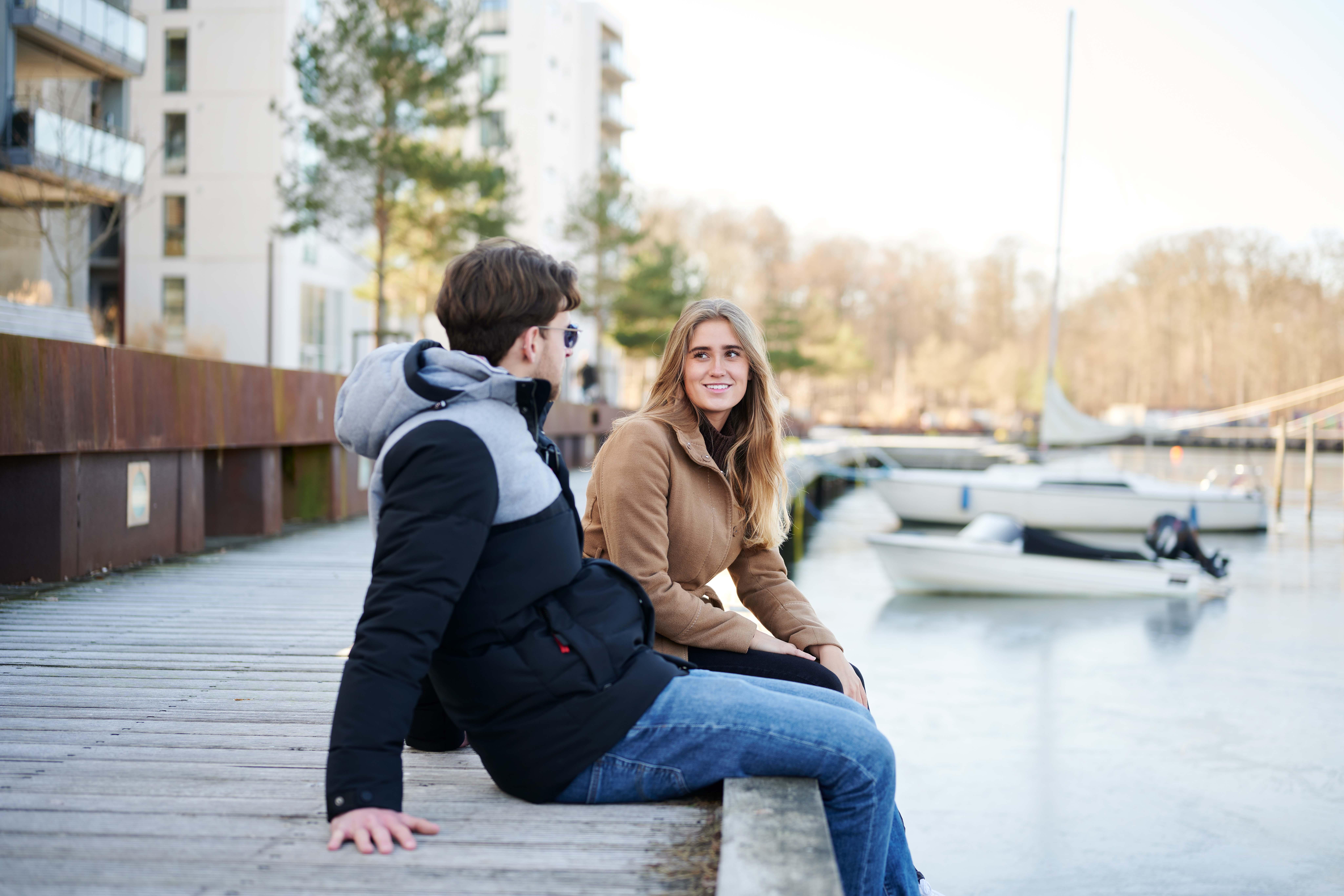 Mand og kvinde sidder ved havnen