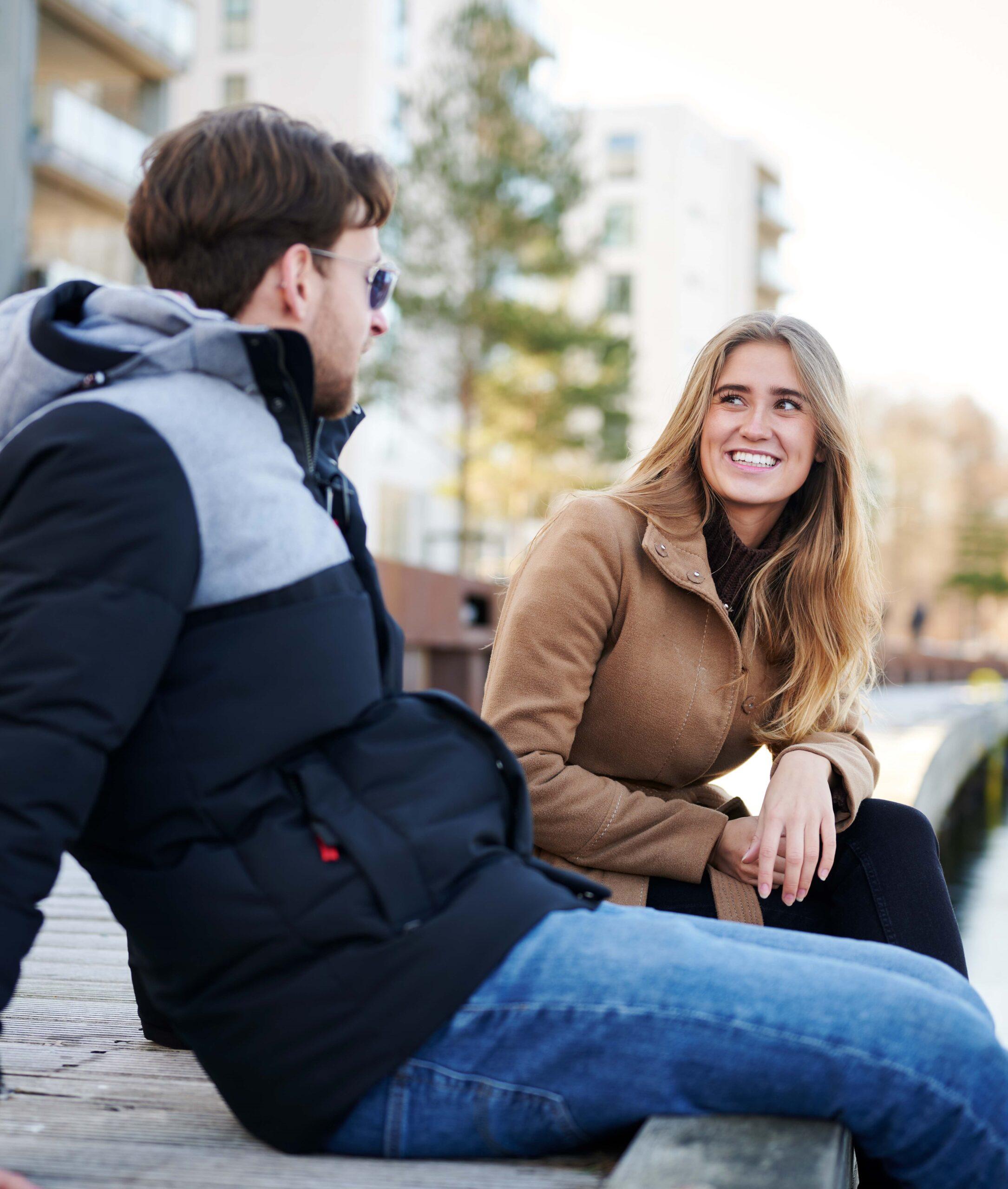 Kvinde og mand sidder og snakker ved havnen