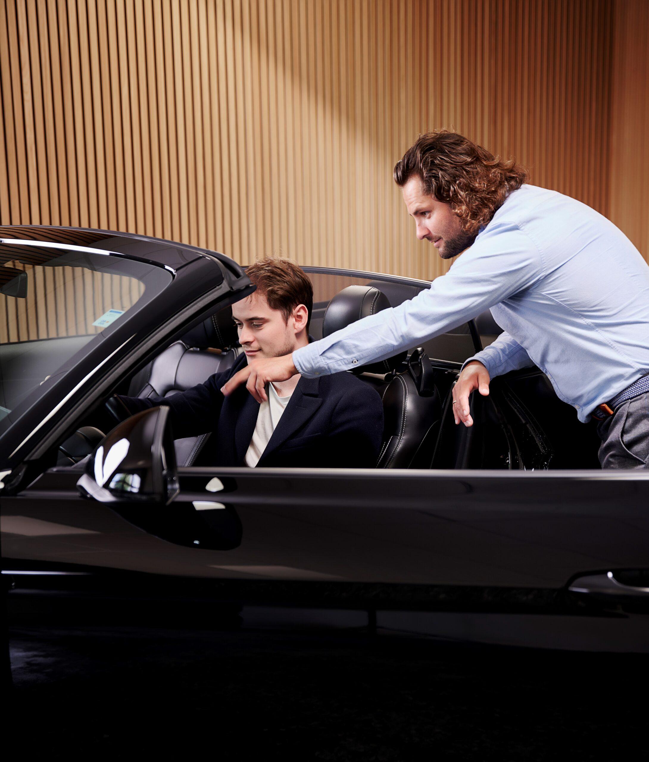 Rådgiver viser en bil frem til en kunde