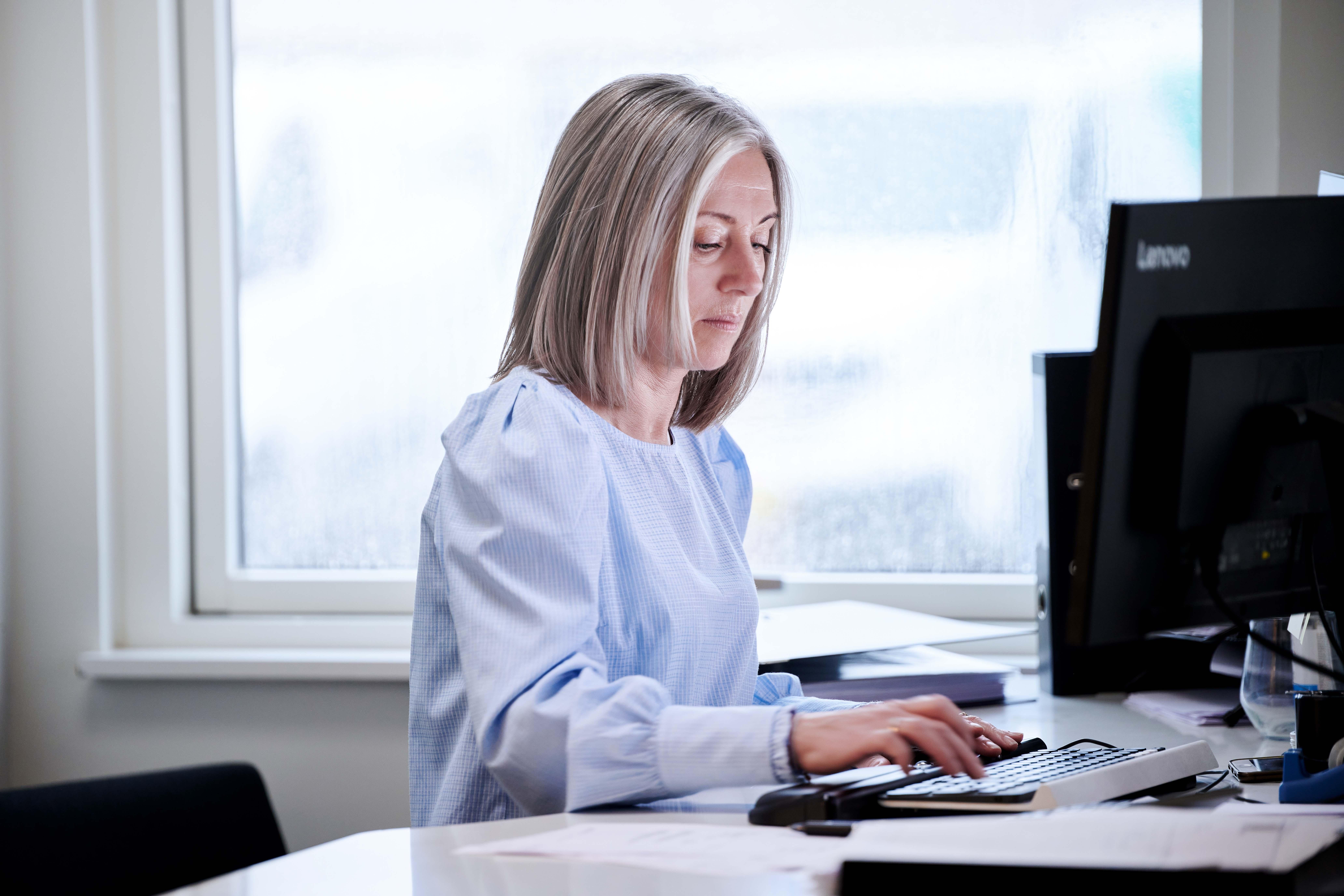 Kvinde sidder ved computer og laver administrativt arbejde
