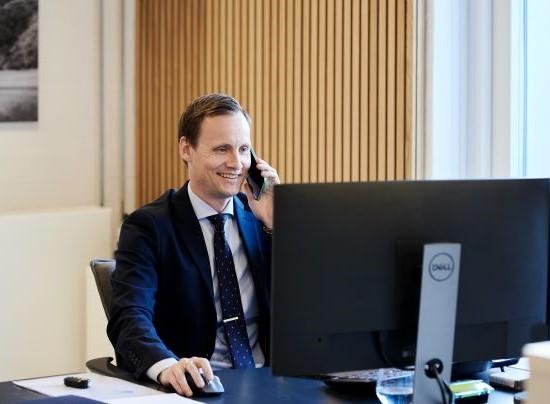 Rådgiver sidder og snakker i telefon foran computer