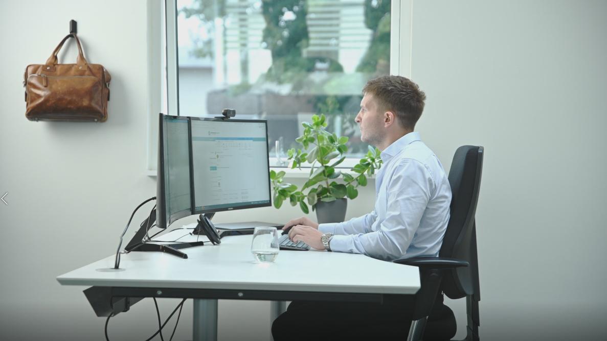 Mand sidder ved computer på kontor