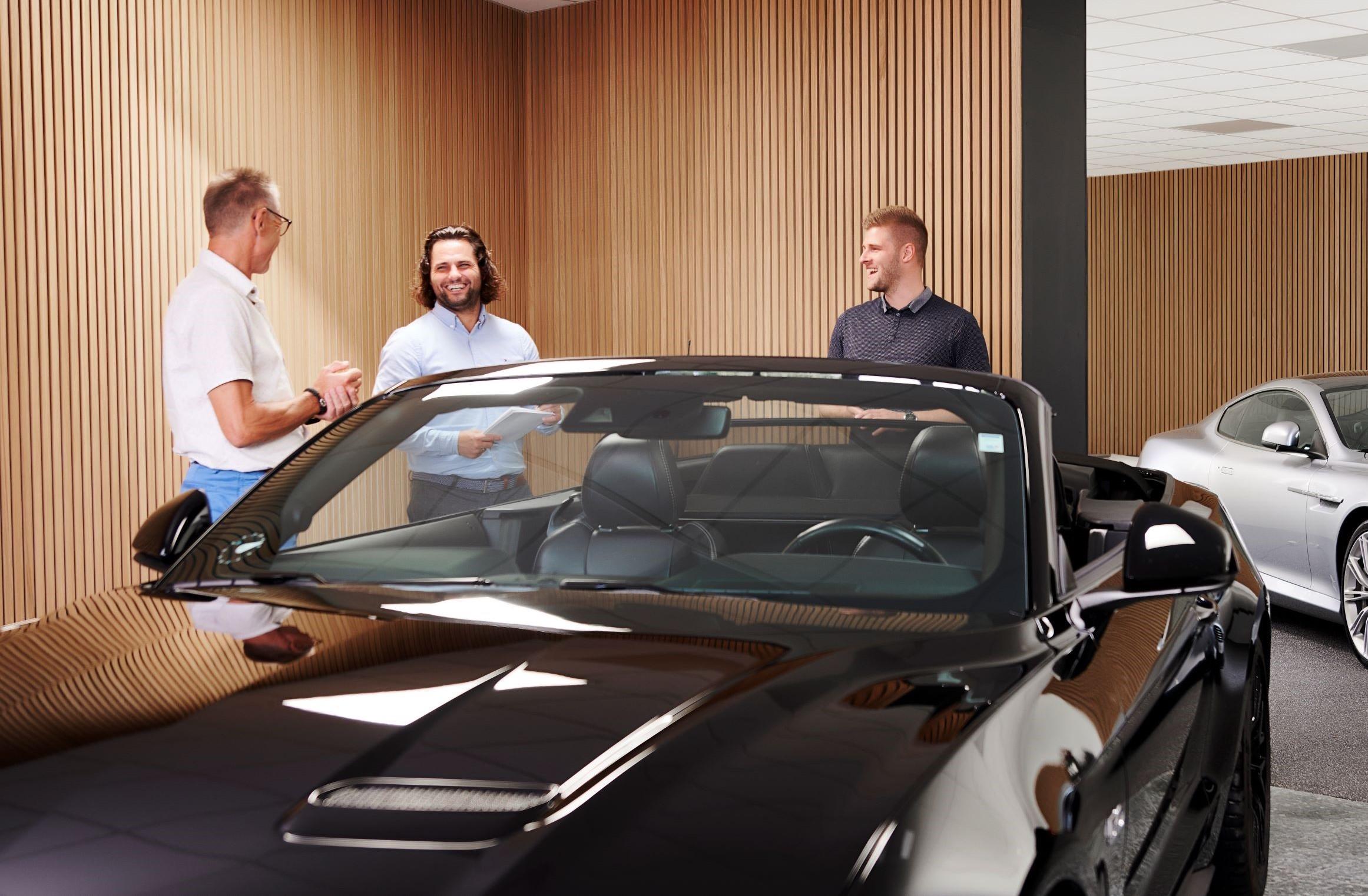 Tre mænd står og snakker henover en sort bil