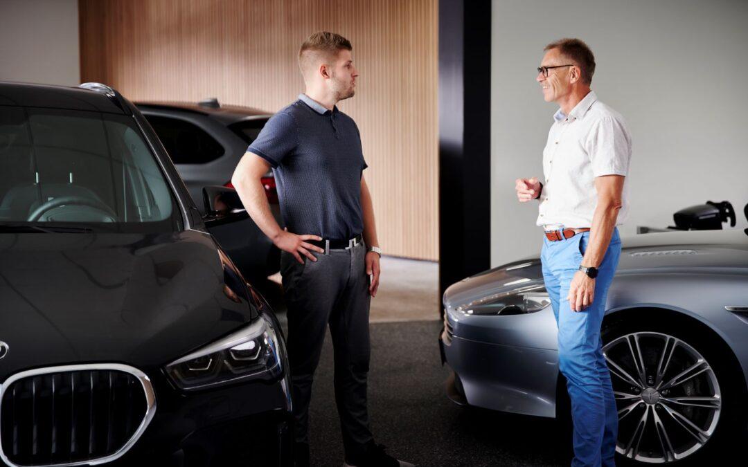 To mænd snakker med biler i baggrunden