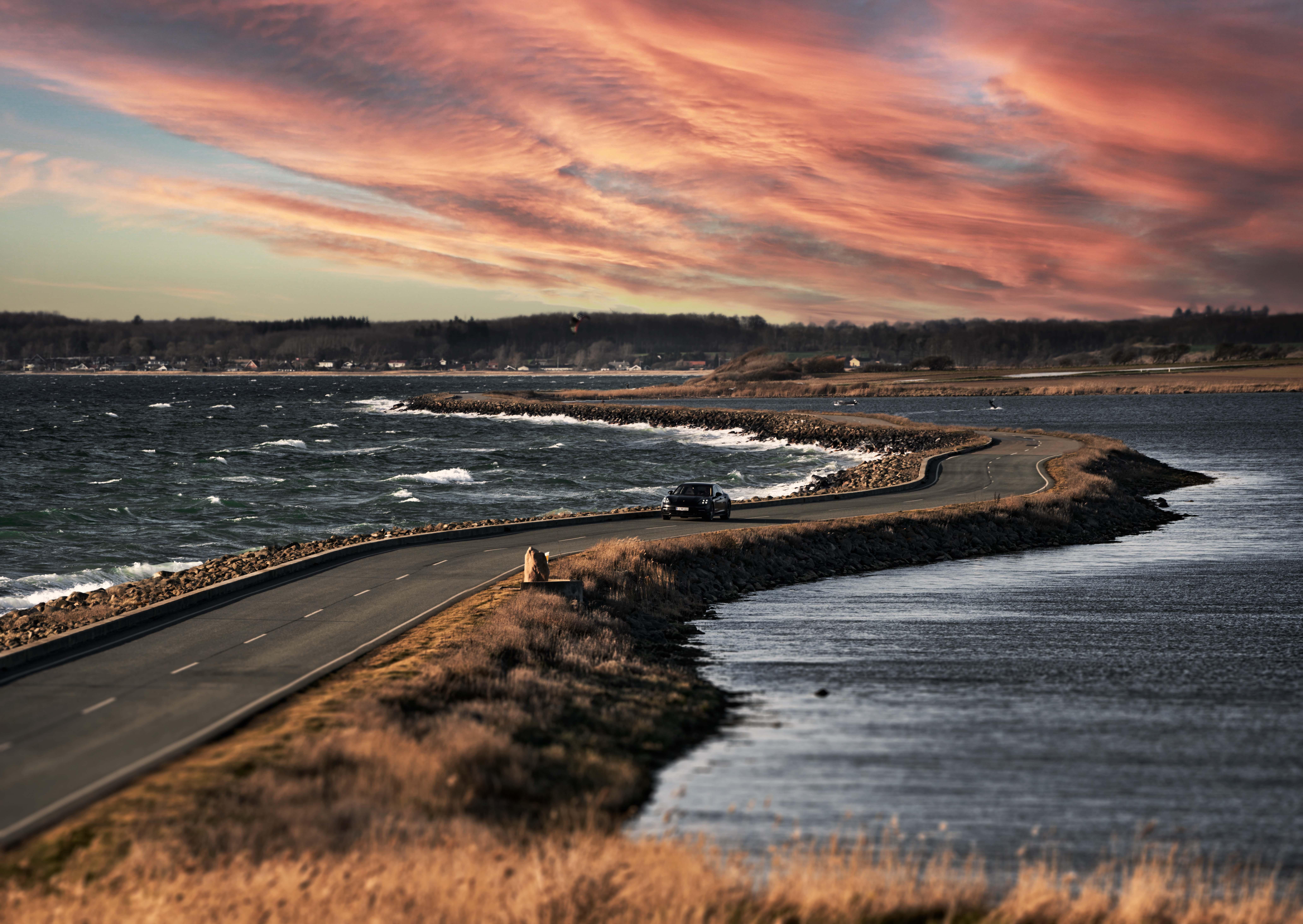 Bil kører på vej med hav på begge sider